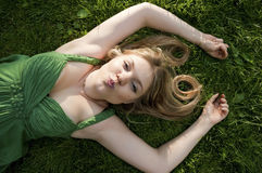 Sexy young blond woman laying on green grass Royalty Free Stock Image