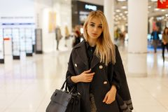 Sexy young blond woman model in a chic fashionable coat with a fashionable leather black fashion handbag royalty free stock image