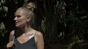 Sexy young blonde beauty looking around in a rain forest. stock video footage