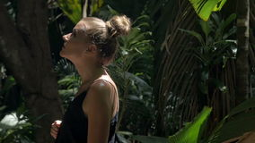 Young blonde beauty looking around in a rain forest. Attractive young woman among the tropical plants. Vacation. Tropics. Beautiful woman standing in the jungle stock video