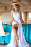 Sexy young blonde bride in a cruise wedding white dress in a summer sea restaurant. Fashion beauty portrait Royalty Free Stock Photos