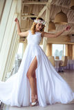 Sexy young blonde bride in a cruise wedding white dress in a summer sea restaurant. Fashion beauty portrait Stock Photography