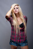 Sexy  young blonde female against grey Royalty Free Stock Image