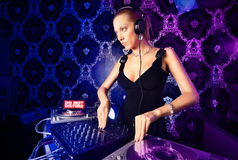 Sexy young blonde lady DJ playing music. In night club Royalty Free Stock Image