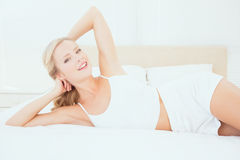 Sexy young blonde lying on her bed smiling at camera Stock Image