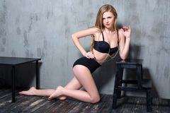 Sexy young blonde woman in black luxury lingerie posing against grungy gray wall. Passion and desire pose. Attractive Royalty Free Stock Photography