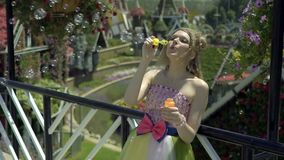 young blonde woman blowing soap bubbles in flower garden. Pretty dreaming cute girl in funny lace dress relaxes stock video