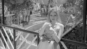 young blonde woman blowing soap bubbles in flower garden. Pretty dreaming cute girl in funny lace dress relaxes stock video footage