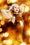 Blond woman on golden background. Young blonde woman dancing on golden background royalty free stock image
