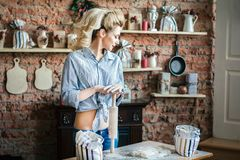 young woman blonde erotic prepares dough in the kitchen. housewife with bags of flour and with rolling pin in the kitchen royalty free stock photography