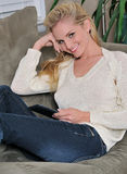 young blonde woman laying on couch - tablet Stock Image