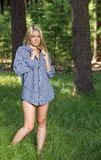 Sexy young blonde woman in men's shirt. Stunning young blonde woman in a pine forest wearing only a men's shirt Royalty Free Stock Photo