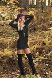 Blonde woman poses in black dress and boots. Young blonde woman in stunning black dress and over the knee boots wears a colorful hat in the autumn woods - fall stock photo