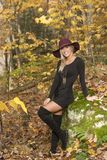Blonde woman poses in black dress and boots. Young blonde woman in stunning black dress and over the knee boots wears a colorful hat in the autumn woods - fall royalty free stock images