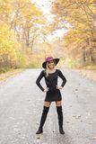 Blonde woman poses on country lane in fall. Young blonde woman in stunning black dress and over the knee boots wears a colorful hat standing on deserted country royalty free stock photography