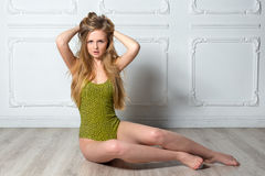 young blonde woman in swimsuit posing against Royalty Free Stock Photos