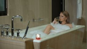 young blonde woman is taking foamy bath, relaxes and enjoys, drinks white wine, girl is drinking champagne in stock video