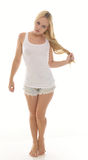 Sexy young blonde woman in white tank top and shorts. Sexy young blonde woman posing on stool in white tank top and jean shorts - tugging on her hair while Royalty Free Stock Image