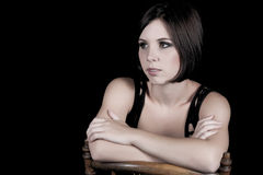 Sexy young brunette on a chair. Sexy young brunette sitting on a chair on a black background in studio Royalty Free Stock Photo
