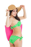 young  brunette girl wearing green swimsuit and big hat, ho Stock Photos
