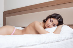 Sexy young brunette lying on bed, close-up Stock Photos
