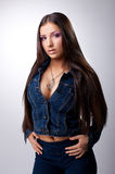 Sexy young brunette posing in jeans costume Stock Photography