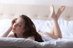 young brunette posing lying in hotel bed Stock Images