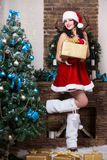 Young brunette. Posing near christmas decorations wearing like Santa`s helper royalty free stock photo