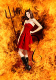 Young brunette woman as devil in fire. With horns, trident and tail royalty free stock photo