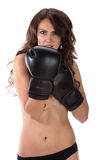 Sexy young brunette woman with black boxing gloves covering brea Royalty Free Stock Image