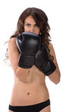 Sexy young brunette woman with black boxing gloves covering brea Stock Image