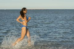 A sexy young brunette woman or girl wearing a bikini running through the surf on a deserted tropical beach with a blue sky. Young stock photography