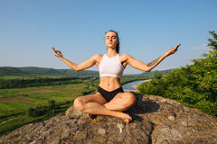 Sexy young brunette woman with muscular body practicing yoga on the rock. Blue sky background. Harmony and relaxing Stock Image