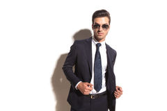 Sexy young business man with sunglasses opening his coat. On white studio background Stock Image