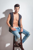 Sexy young casual man sitting on a wood stool Royalty Free Stock Photos