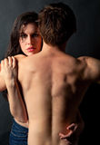Young Couple. A portrait of a gorgeous young woman hugging a man with a strong, back stock photography