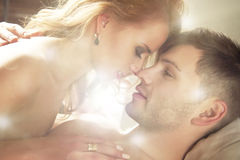 Sexy young couple kissing and playing in bed. Royalty Free Stock Photography
