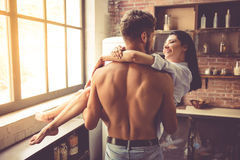 Sexy young couple in kitchen. Sexy young men with bare torso is holding his beautiful girlfriend in arms while standing in kitchen at home. Both are looking at Royalty Free Stock Photo