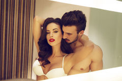 Sexy young couple in mirror at home Stock Images