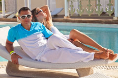 Sexy young couple relaxing near pool on a beach bed Stock Images