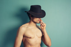 Sexy young cowboy smoking cigarette Stock Photography