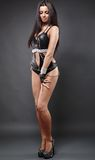 Sexy young exotic dancer in black latex lingerie on gray backgro Royalty Free Stock Images