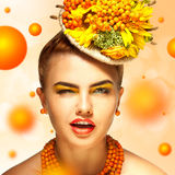 Young fashion girl with beautiful makeup blink. On orange background royalty free stock photo