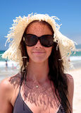 Sexy young female on beach with hat. Attractive girl wearing hat and sunglasses on holiday at sunny beach Stock Photo