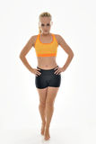 Sexy young female fitness model - petite. Sexy young blonde woman in bright sports bra and work-out shorts stands barefoot in studio (fitness Royalty Free Stock Image