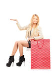 A sexy young female gesturing next to a shopping bag. On white background Royalty Free Stock Photography