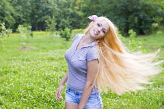 Sexy young female smiling in a park Royalty Free Stock Image