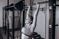 Young fit woman doing pull-up on on a crossbeam - horizontal bar. Strong Female fitness at gym. Young fit woman doing pull-up on on a crossbeam - horizontal bar royalty free stock images