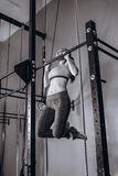 Sexy young fit woman doing pull-up on on a crossbeam - horizontal bar. Strong Female fitness at gym. Sexy young fit woman doing pull-up on on a crossbeam Royalty Free Stock Images