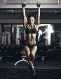 Sexy young fitness girl pulls up in the gym. Stock Photos
